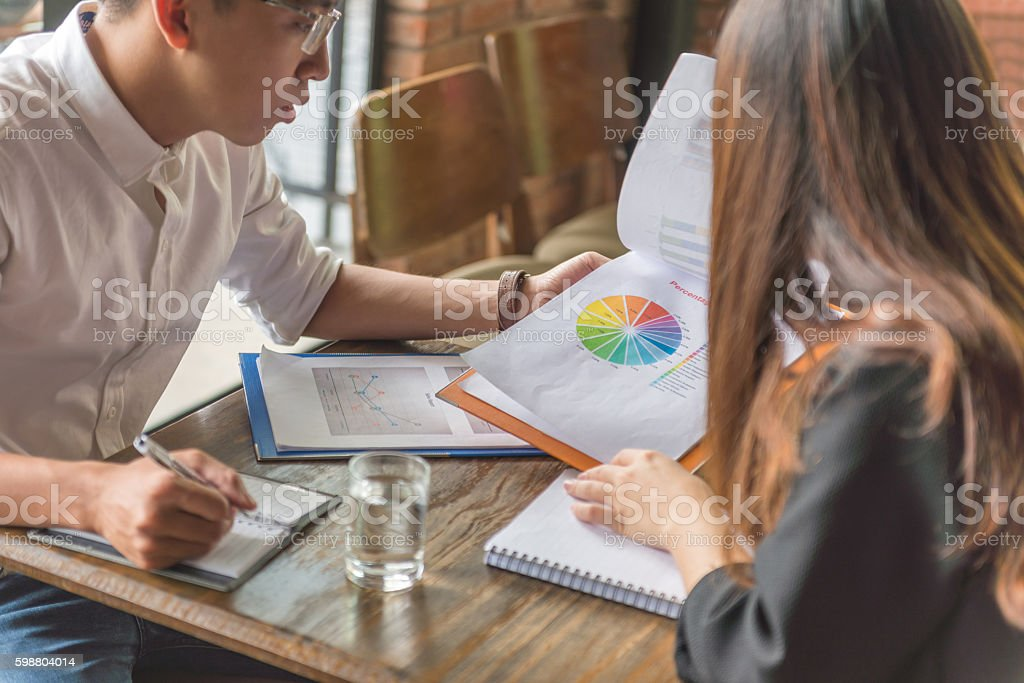 Man and woman working together on income rate report stock photo