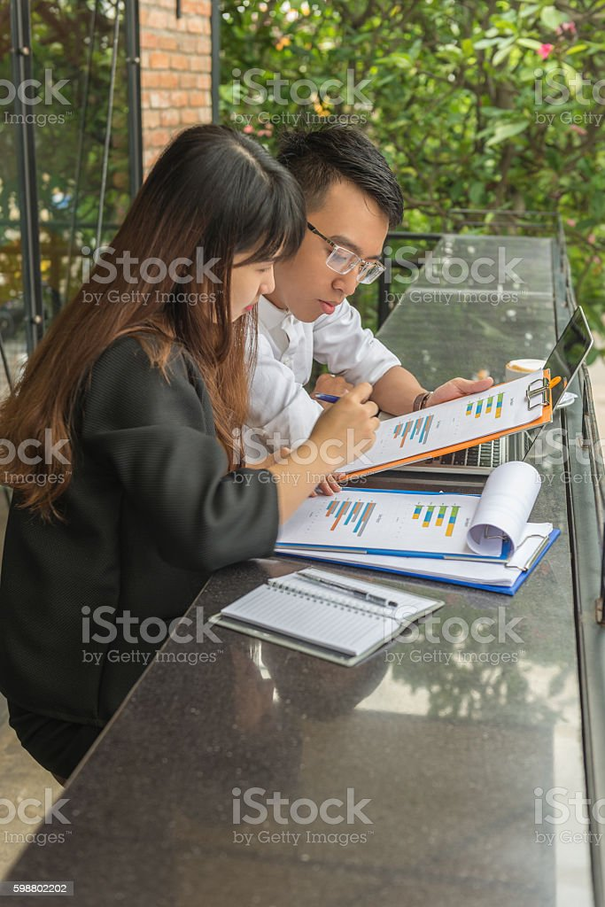 Man and woman working together on monthly sales report stock photo