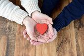 心臓の物体を持つ男女の手