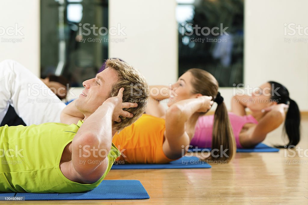 Man and women doing sit-ups at a gym for fitness stock photo