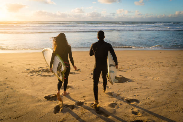 Man And Women Surfers Running To The Water stock photo