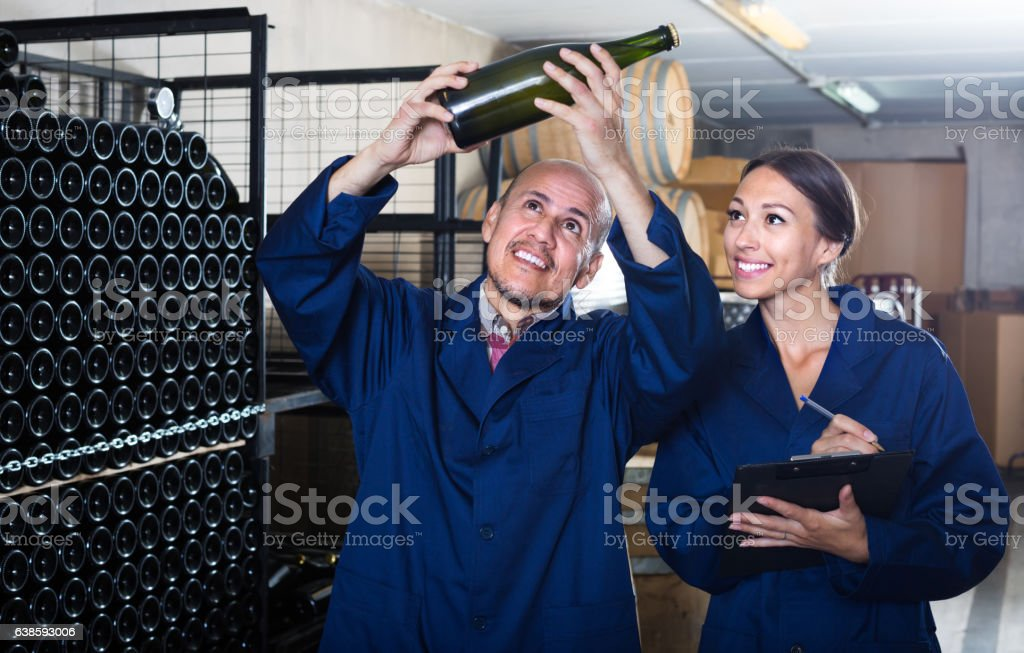 man and women winemakers with wine bottle stock photo