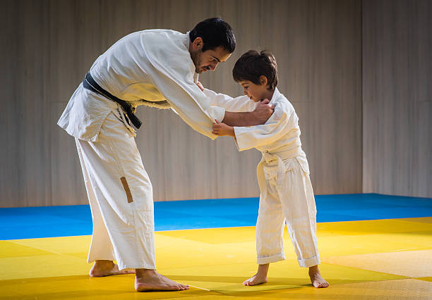 Man and young boy are training judo throw - foto de stock