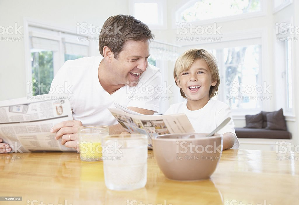 Man and young boy in kitchen reading newspaper and laughing stock photo