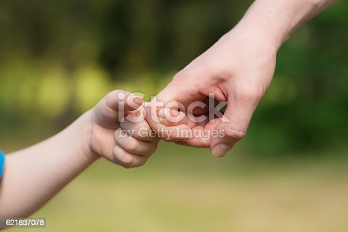 istock Man and young boy play with hands 621837078