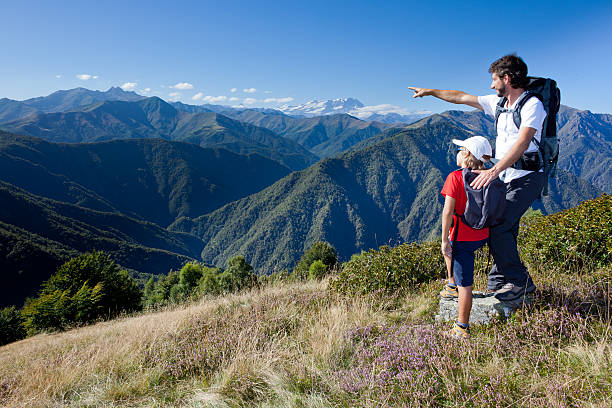 Man and young boy standing in a mountain meadow stock photo