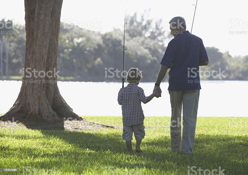 Hombre y joven niño con pesca polos al aire libre en el parque - foto de stock