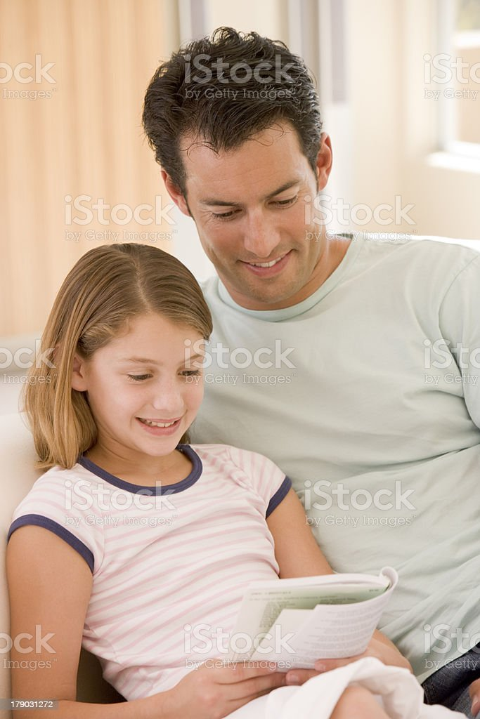 Man and young girl in living room reading book royalty-free stock photo