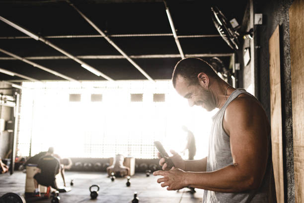 Man answering messages on iphone at the gym stock photo