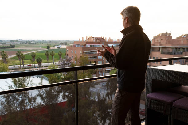 Man applauding from his balcony in Spain to support medical staff due coronavirus pandemic stock photo
