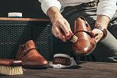 男は靴を磨く小さなブラシで適用します。