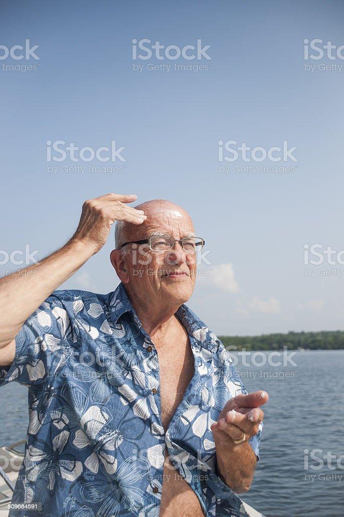 Man applies sunscreen to bald head stock photo