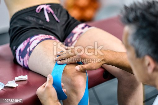 Man applying blue Kinesio tape for fixation of woman's knee. Physiotherapy, massage, medical care concept.