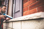 Man applying caulking around window frame to weather seal it for the winter