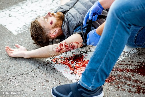 istock Man applying first aid to the bleeding person on the road 1162084785