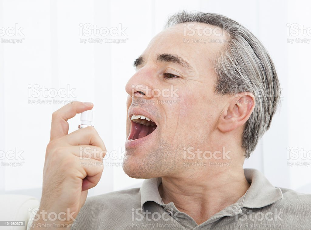 Man applying Fresh breath spray stock photo