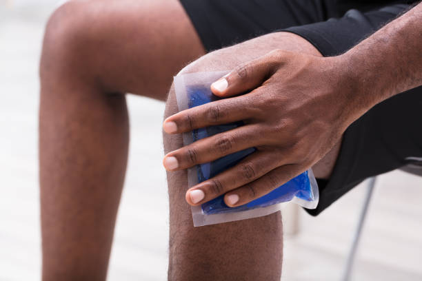 man applying ice gel pack on his knee - crioterapia foto e immagini stock