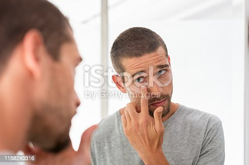 Young man taking care of his undereye wrinkles putting anti aging eye moisturizer. Man applying skincare facial treatment cream on face in the bathroom. Handsome guy applying moisturizer and looking at himself while standing in front of the mirror.