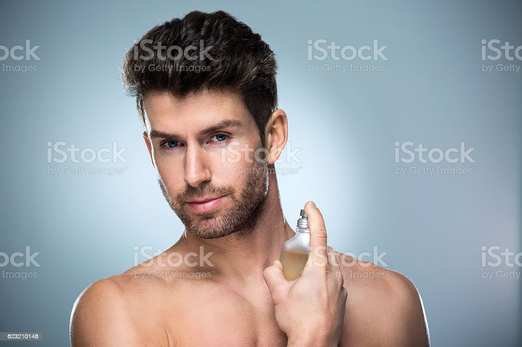 Man applying perfume to his neck stock photo