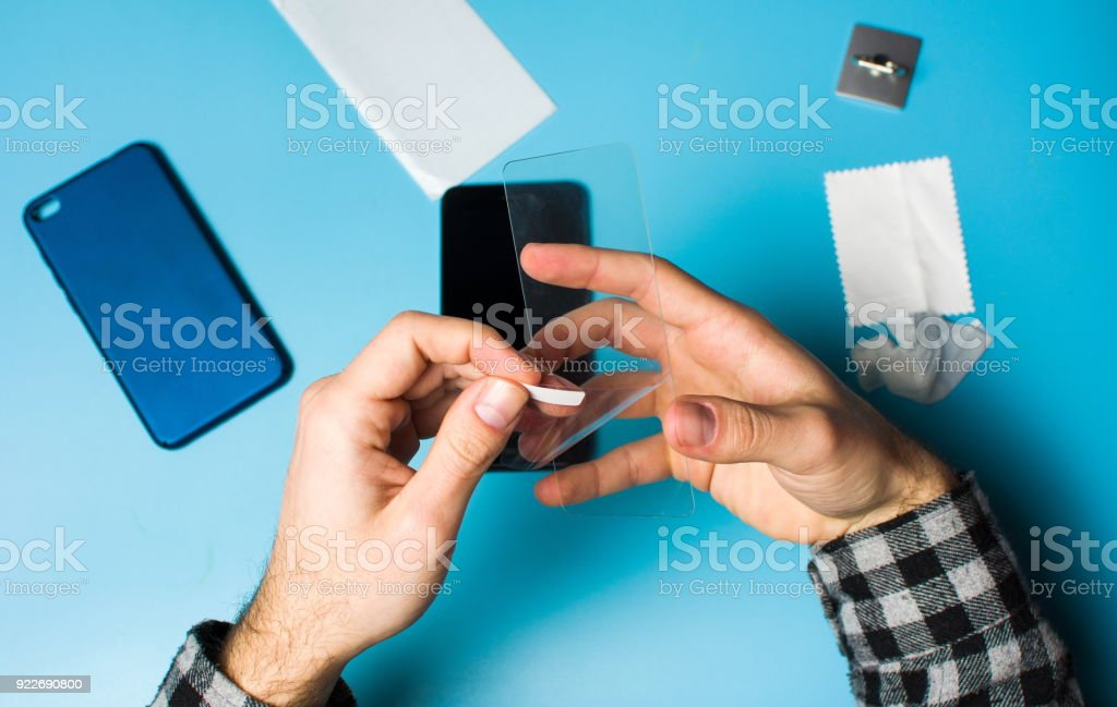 Man applying protective tempered glass to phone screen stock photo