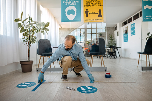 Man measuring and applying social distancing sign on reopening at office