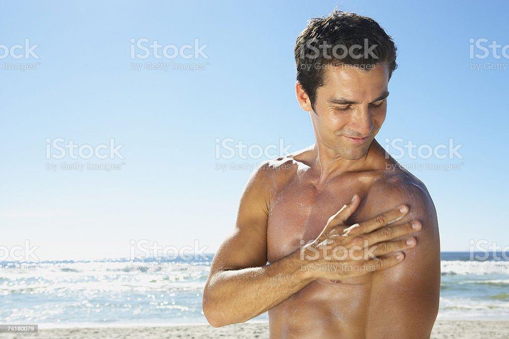 Homem aplicando sol bloquear ou protetor solar ao ar livre foto de stock royalty-free