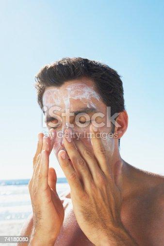 istock Man applying sun block or suntan lotion to face 74180080
