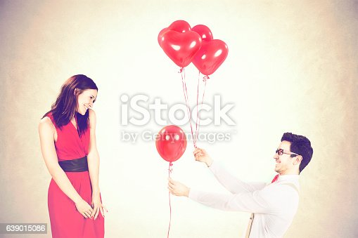 istock Man approaching woman giving her red heart shape balloons 639015086