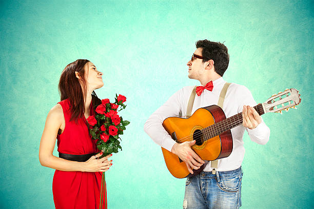 Man approaching woman playing a love song, serenade Funny Valentine's Day, series of different approaching acts serenading stock pictures, royalty-free photos & images
