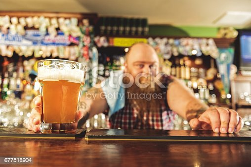 istock Man arm putting alcohol beverage in alehouse 677518904