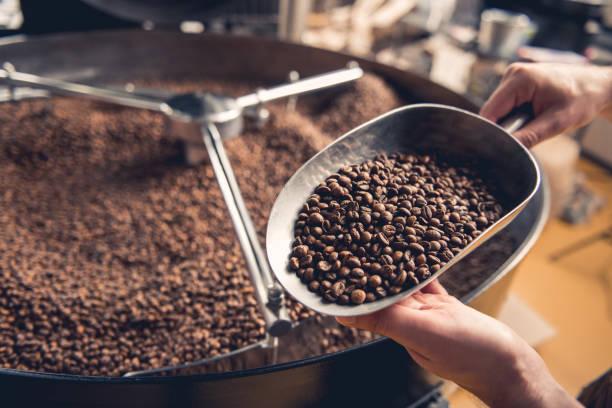 굽는 기계 근처 곡물을 들고 남자 팔 - coffee 뉴스 사진 이미지