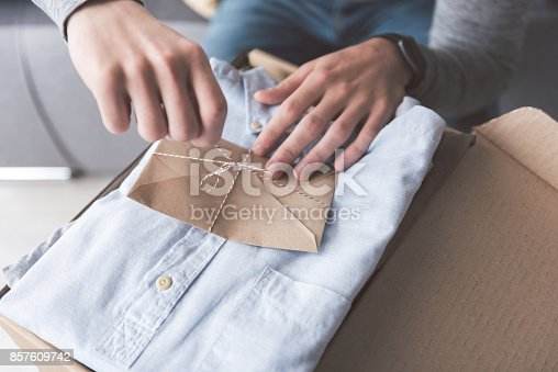 istock Man arms untying letter on clothes 857609742