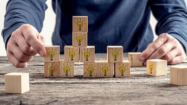 Homme place blocs en bois jaune des ampoules dessinés à la main - Photo