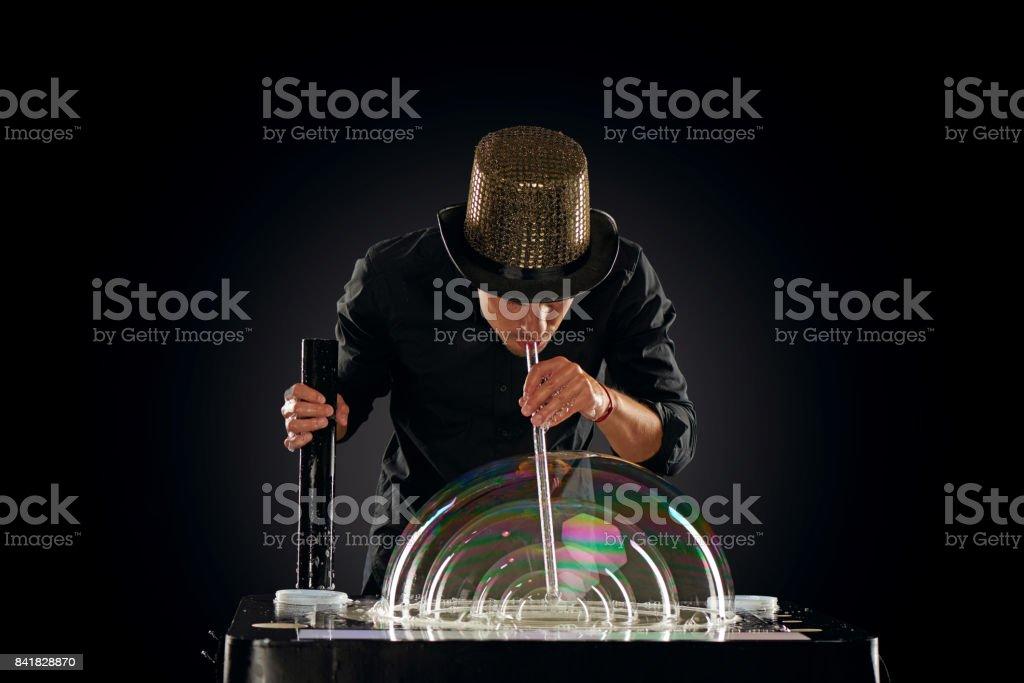 Man artist blowing many soap bubble. Soap bubble show in black studio. stock photo
