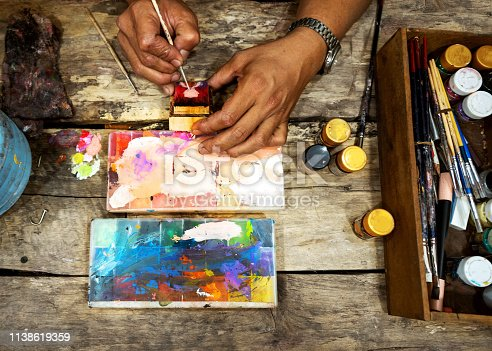 181894581 istock photo man artist creates a painting by drawing an abstraction. working environment in the office, top view. 1138619359