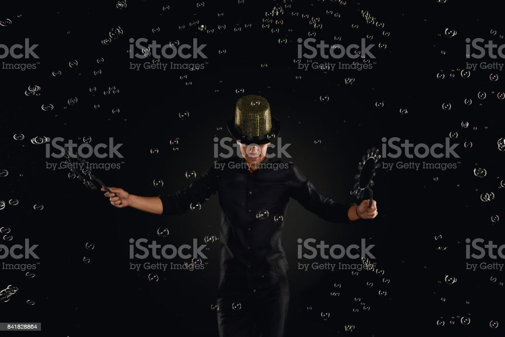 Man artist fiddle with many soap bubble. Soap bubble show in black studio. stock photo