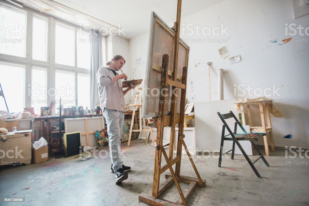 Man artist paints in his workshop stock photo