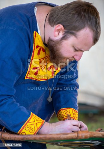Lismore,NSW,Australia:June 22,2019.  Man as a Viking villager works on his shield at the Viking Festival. Every year,on the Winter solstice, a group of Viking followers build a Viking village in the NSW town of Lismore. For two days they live as Vikings, dressing ,playing ,eating, speaking, fighting as the ancient Vikings did. This event is free and open to the public. It is held on a recreation ground in the town.