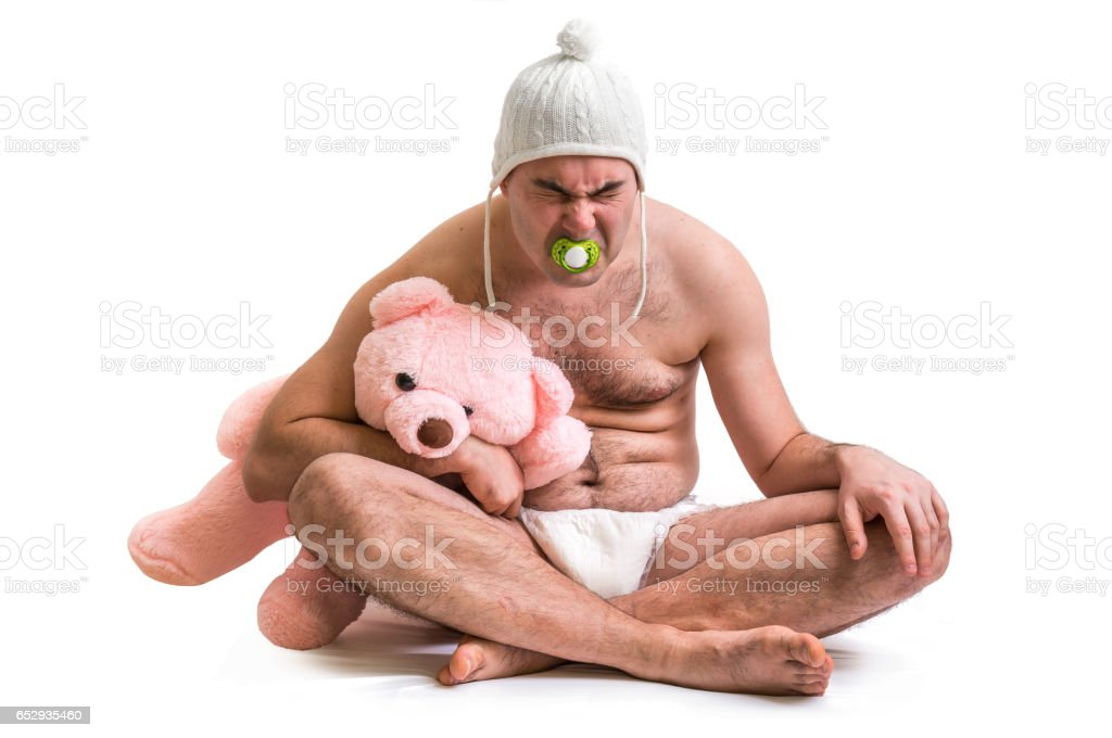 Man as baby. Child in diaper with pink teddy bear. stock photo
