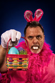 A middle aged man dressed up as a Deranged Easter Bunny with a pink shirt, boa, Bunny ears and buck teeth, offering a small Easter Basket with colored eggs, against a blue background