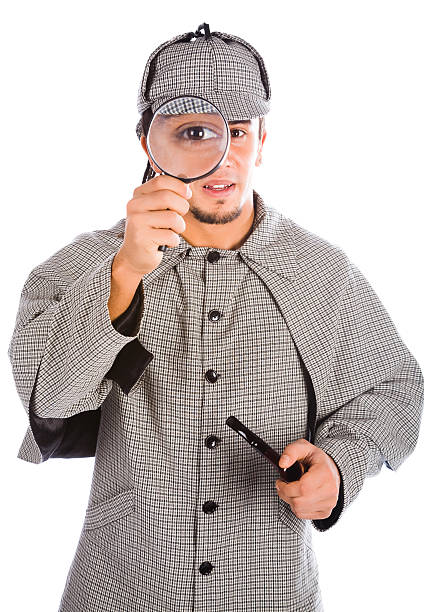 Man as Sherlock Holmes looking through a magnifying glass stock photo