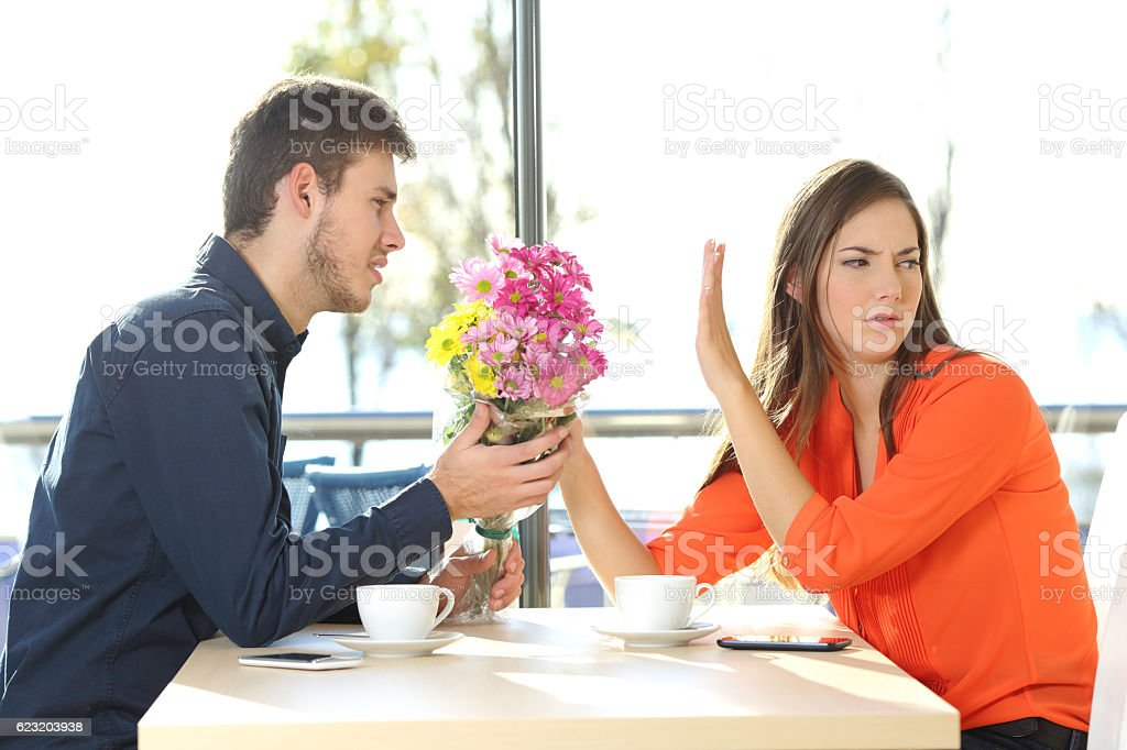 Man asking for forgiveness to his girlfriend stock photo