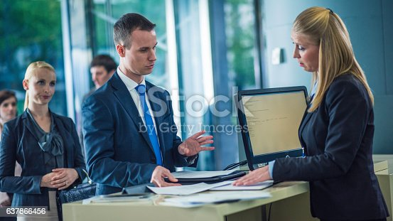 istock Man asking questions at a bank counter 637866456