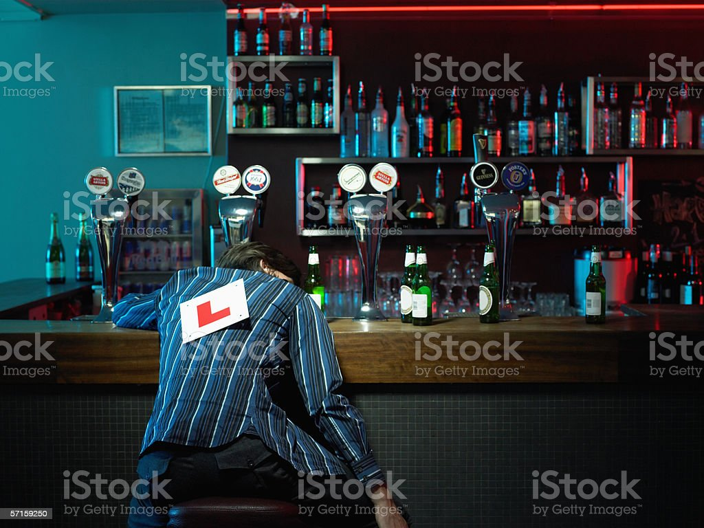 Man asleep at bar stock photo