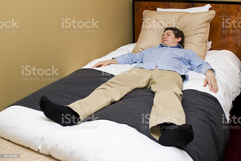 Man Asleep on Hotel Bed royalty-free stock photo