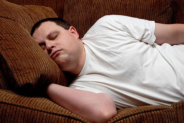 uomo addormentato su un divano - divano procrastinazione foto e immagini stock