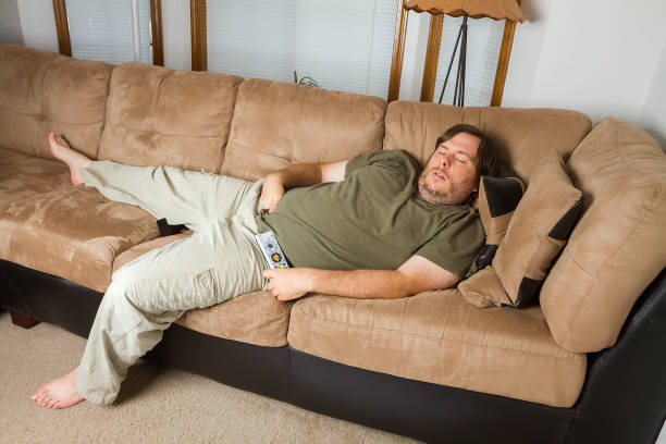 Man asleep on the couch stock photo