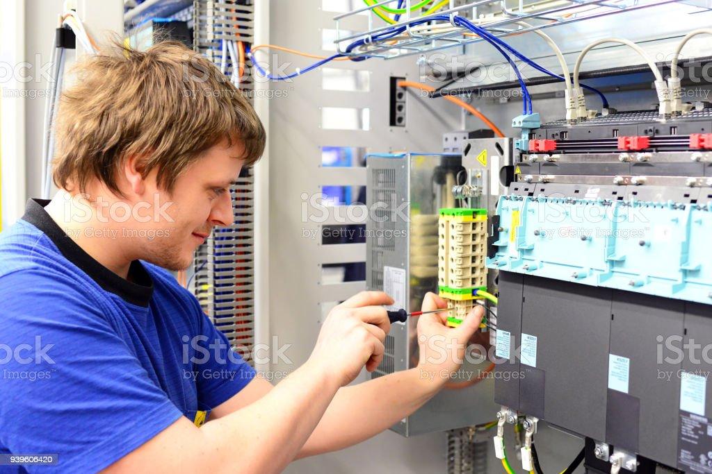 Mann baut elektronische Komponenten auf einem Computer in einer Fabrik für Maschinenbau Lizenzfreies stock-foto