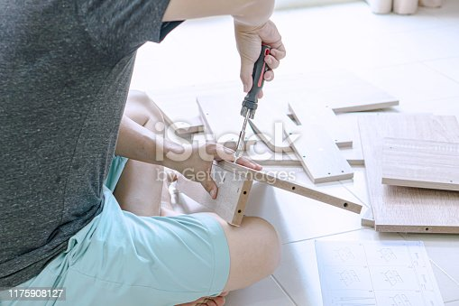 459373065 istock photo Man assembling furniture in his new home 1175908127