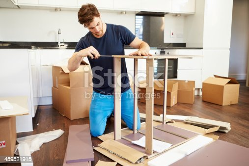459373065 istock photo Man assembling furniture in his new home 459521915